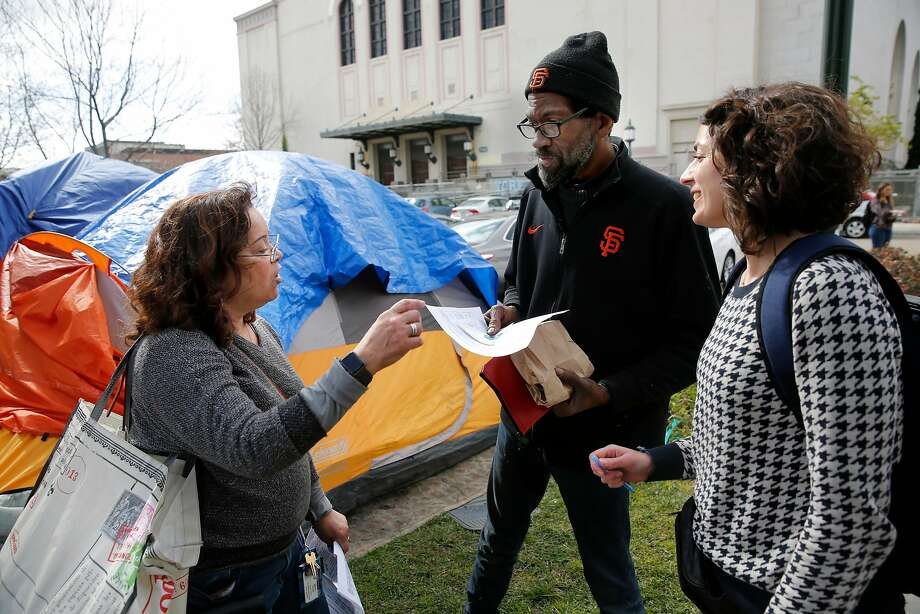 Wilma Lozada (left), an outreach team member, and Dr. Aislinn Bird talk with Pastor Preston, (center) during a visit to a homeless encampment near Lake Merritt in Oakland. Photo: Michael Macor, The Chronicle