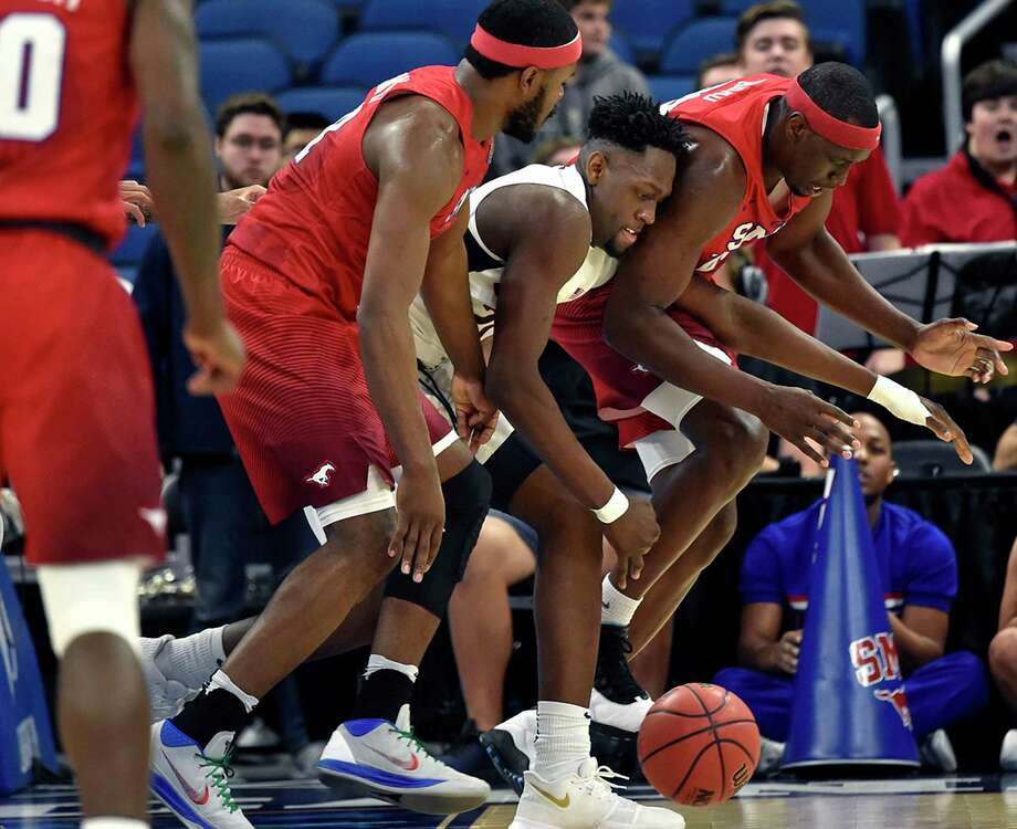 Connecticut Huskies forward Mamadou Diarra (21) battles Southern Methodist Mustangs guard Ben Emelogu II (21), left, and Southern Methodist Mustangs forward Akoy Agau (23) for a loose ball in a first round game at the 2018 American Athletic Conference Men's Basketball Championship at Amway Center Thursday, March 8, 2018 in Orlando. SMU won, 80-73. Photo: Brad Horrigan, TNS / Hartford Courant