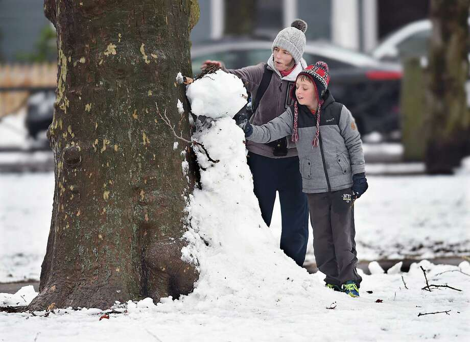 Jack Turner, 10 and his mother Karen Turner build a snowman against a tree in Wooster Square Park, Thursday, March 8, 2018, following the nor'easter. The Turners are visiting from Northern Ireland for a few months. Photo: Catherine Avalone, Hearst Connecticut Media / New Haven Register