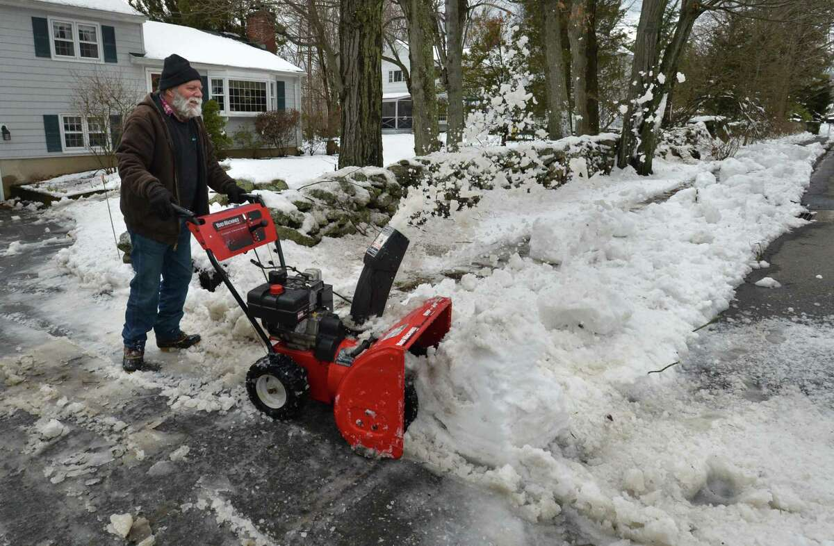 Tim Caputo clears the snow from his driveway and sidewalk after Wednesday's winter storm on Thursday in Norwalk.