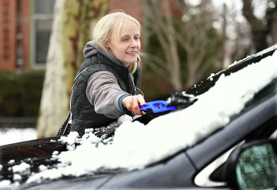 Kathryn Blair, a graduate student at Yale University, from Utah, clears now off her windshield of her SUV in Wooster Square, Thursday, March 8, 2018, following the nor'easter. Blair said the residents living on her side of Wooster Square lost power at about 7 p.m. and it returned around 3 a.m. Photo: Catherine Avalone, Hearst Connecticut Media / New Haven Register