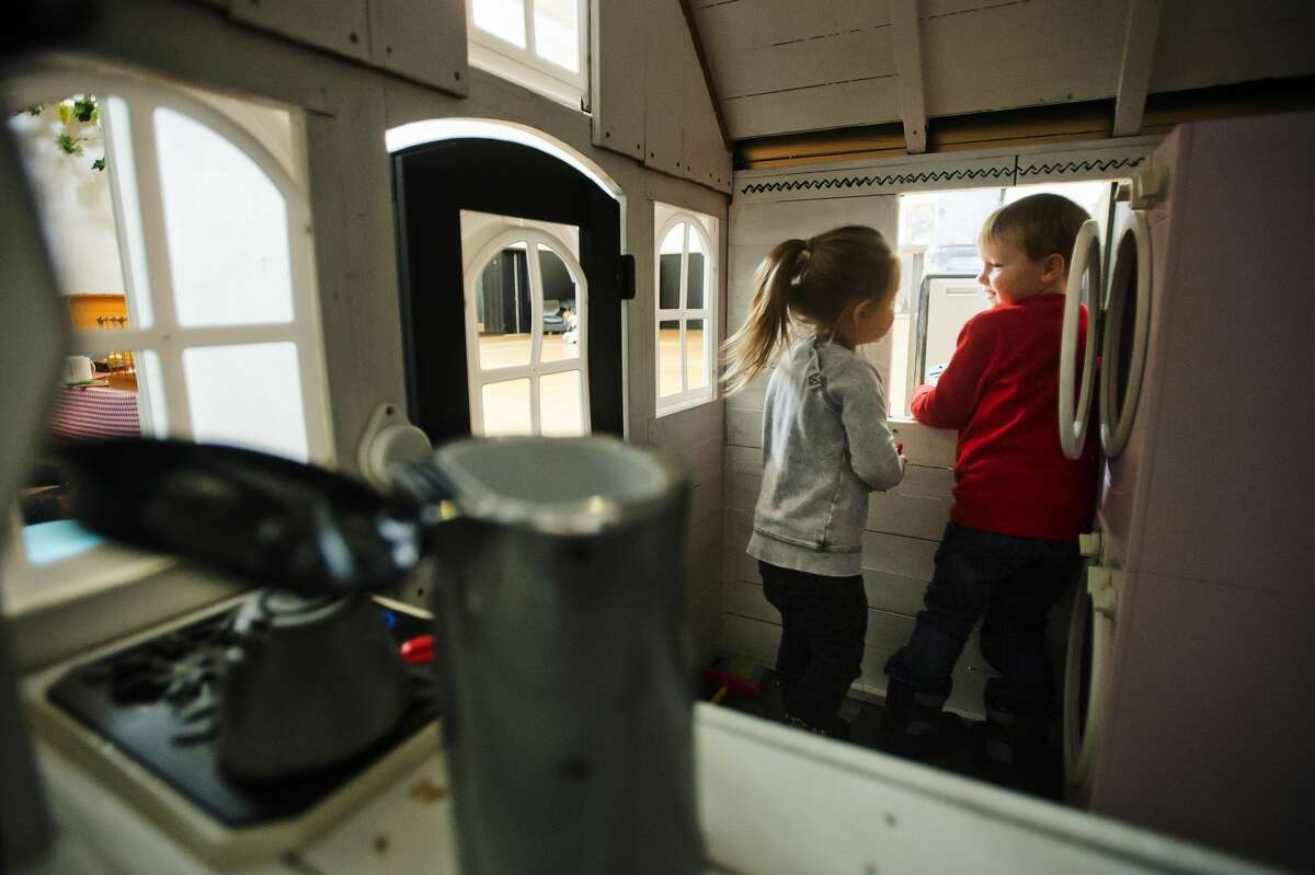 Brooklynn White, 2, left, and Florian Sanders, 3, both of Midland, play together inside a miniature house at Little Midland, a miniature play city modeled after local businesses in Midland, on Wednesday, March 7, 2018. Little Midland is located on the second floor of Ashman Plaza. (Katy Kildee/kkildee@mdn.net)