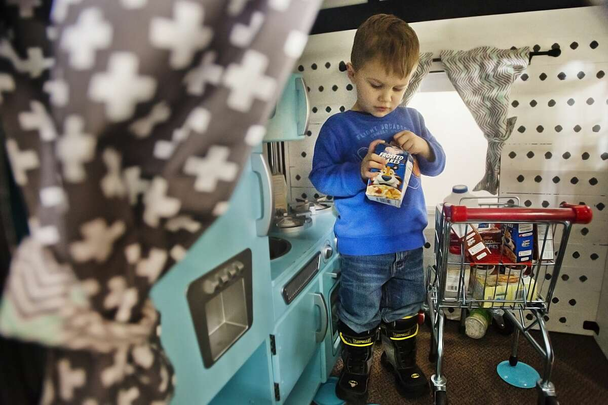 Zane Gregg of Midland, 2, plays inside a miniature house at Little Midland, a miniature play city modeled after local businesses in Midland, on Wednesday, March 7, 2018. Little Midland is located on the second floor of Ashman Plaza. (Katy Kildee/kkildee@mdn.net)