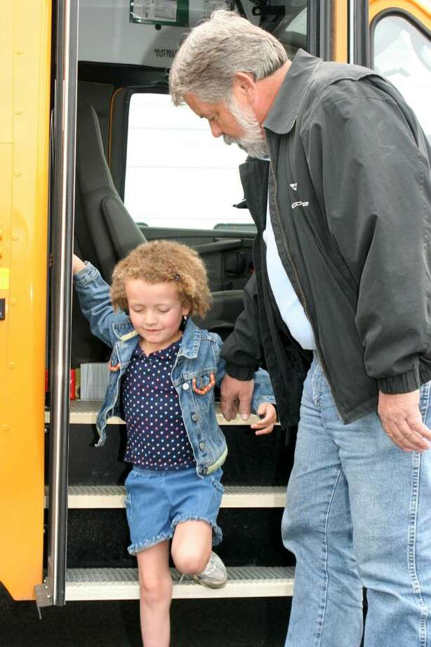 Six-year-old Hannah Sames, left, is helped off the bus by her bus driver Dave Kohls, right, Wednesday morning. The transportation department in the Shenendehowa schools, where Hannah is a kindergartner, donated $2,100 they raised in a bottle drive to help Hannah, who suffers from giant axonal neuropathy, or GAN, a disease that damages the nerve pathways that carry signals to the brain. (Courtesy /  Lori Sames)