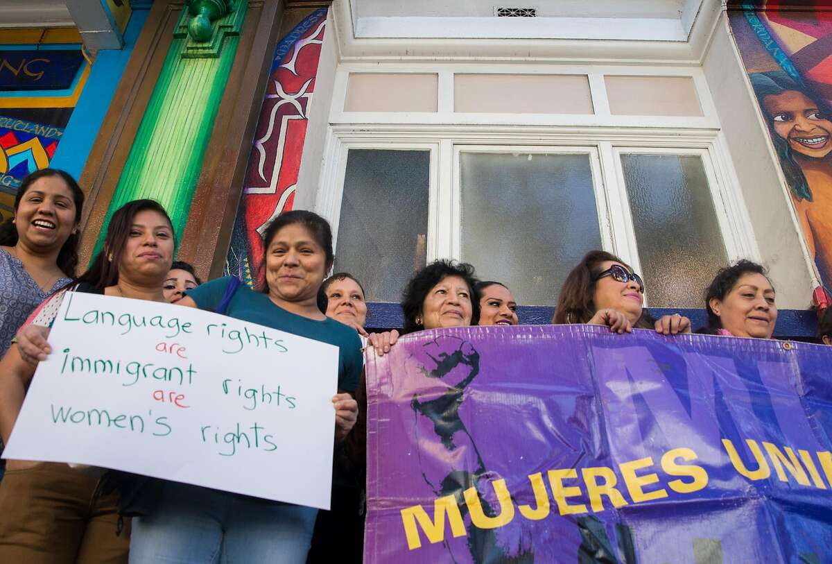 Women with Mujeres Unidasy Activas gather while carrying a banner during a press conference announcing a settlement reached made between San Francisco Police Department and Dora Mejia outside the Women's Building Thursday, March 8, 2018 in San Francisco, Calif.