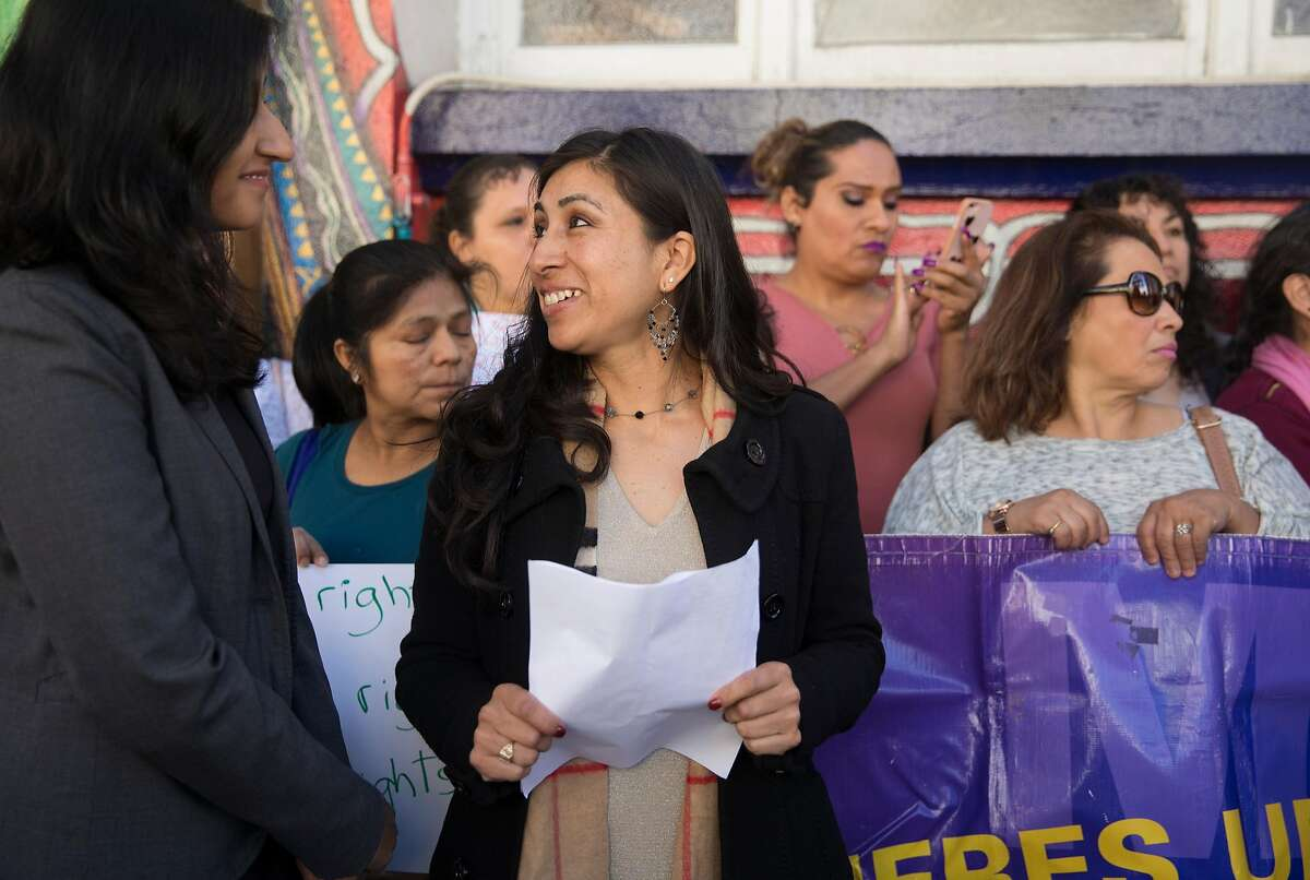Dora Mejia, center, and her attorney, Saira Hussain with Advancing Justice and Asian Law Caucus, left, arrive at a press conference announcing a settlement reached made between San Francisco Police Department and Dora Mejia outside the Women's Building Thursday, March 8, 2018 in San Francisco, Calif.