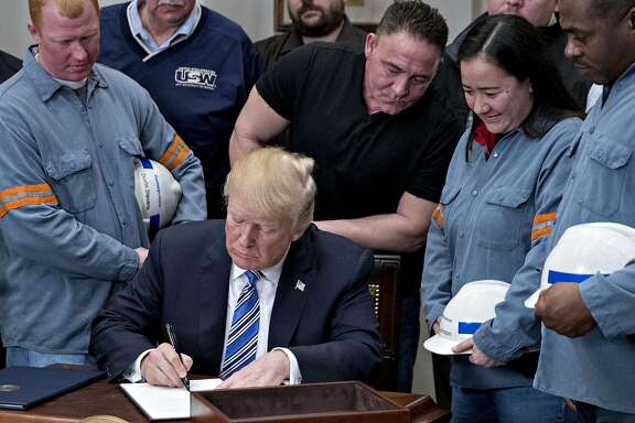U.S. President Donald Trump signs a proclamation on adjusting imports of steel into the United States next to steel and aluminum workers in the Roosevelt Room of the White House in Washington, D.C., U.S., on Thursday, March 8, 2018. Trump signed the order over steel and aluminum tariffs that he said could spare certain countries if they have strong trading and military ties with the U.S. telling reporters earlier that Mexico and Canada would likely not face the levies if they renegotiate the North American Free Trade Agreement. Photographer: Andrew Harrer/Bloomberg
