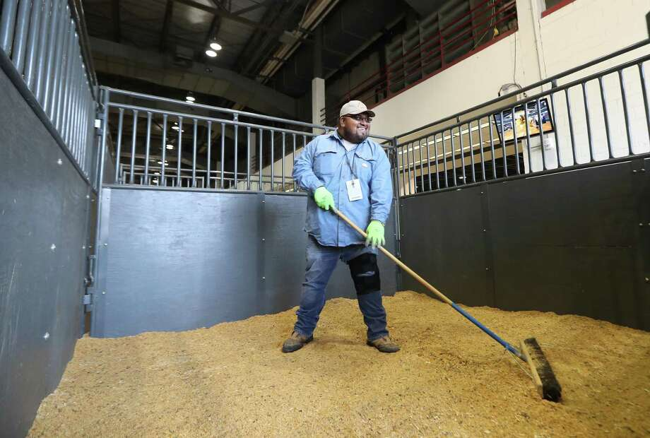 Raul Murillo cleans pens at the Houston Livestock Show Wednesday, March 7, 2018, in Houston. ( Steve Gonzales / Houston Chronicle ) Photo: Steve Gonzales, Houston Chronicle / Houston Chronicle / © 2018 Houston Chronicle