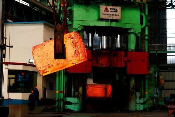 This picture taken on March 5, 2018 shows Chinese employees walking past red hot steel at a steel plant in Zouping in China's eastern Shandong province. A trade war with the US will benefit no one, China warned on March 8, adding it was prepared to give as good as it gets if US President Donald Trump fires the first shots. / AFP PHOTO / - / China OUT-/AFP/Getty Images