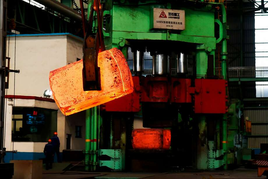 Chinese employees walking past red hot steel at a steel plant in Zouping in China's eastern Shandong province. President Trump has announced plans to impose tariffs on as much as $60 billion worth of Chinese goods, potentially sparking a trade war with the world's second-largest economy. Photo: -, AFP/Getty Images