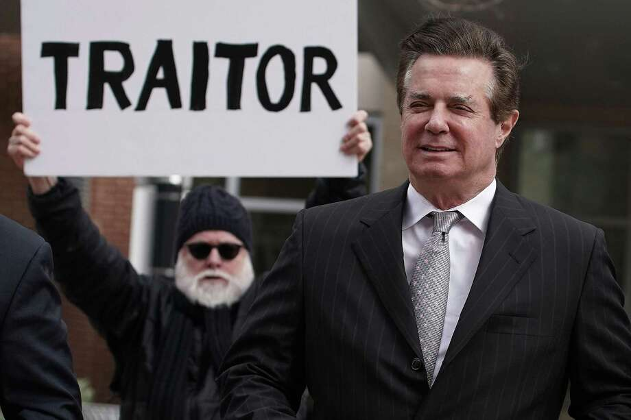 Former Trump campaign manager Paul Manafort (R) arrives at the Albert V. Bryan U.S. Courthouse for an arraignment hearing as a protester holds up a sign March 8, 2018 in Alexandria, Virginia. Manafort was scheduled to enter a plea on new tax and fraud charges, brought by special counsel Robert Mueller's Russian interference investigation team, at the Alexandria federal court in Virginia, where he resides. Photo: Alex Wong /Getty Images / 2018 Getty Images