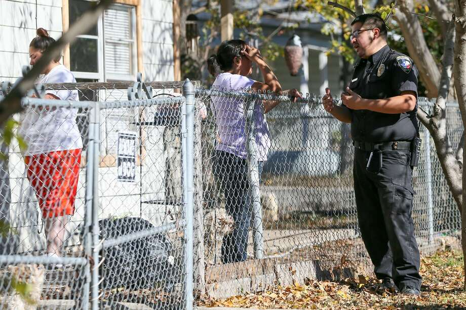 Animal Care Officer Robert Lopez (right) talks to a resident about keeping her dogs confined inside their fence while making his rounds on the southwest side of San Antonio in December. A city program for creating more fencing is being under-utilitzed. Photo: Marvin Pfeiffer /San Antonio Express-News / Express-News 2017