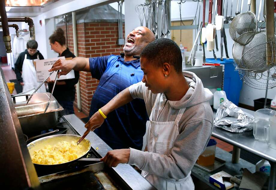 Charles Boomer (left), a student mentor and counselor, prepares lunch for students and faculty at the Life Learning Academy charter school on Treasure Island. He's assisted by culinary class student Tre Jones. Photo: Paul Chinn, The Chronicle