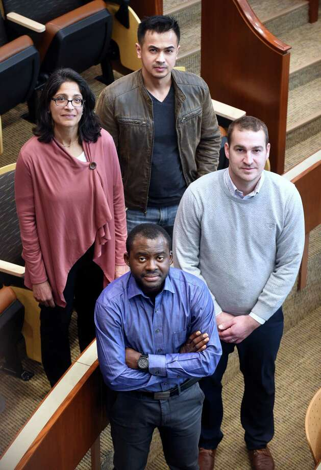 Toto Kisaku, front, of the Democratic Republic of Congo, with,  from left, QuinnipiacLaw professor Sheila Hayre and law students Thai Chhay and Brendan Lawless. Photo: Arnold Gold / Hearst Connecticut Media / New Haven Register