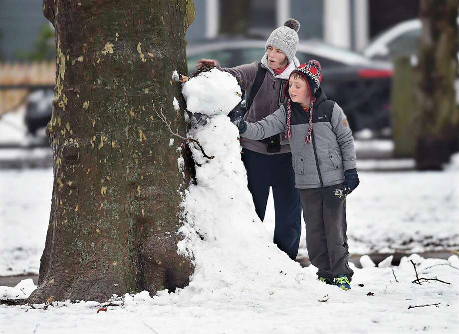 Jack Turner, 10 and his mother, Karen Turner, build a snowman against a tree in Wooster Square Park, Thursday following the nor'easter. The Turners are visiting from Northern Ireland for a few months. Photo: Catherine Avalone / Hearst Connecticut Media / New Haven Register