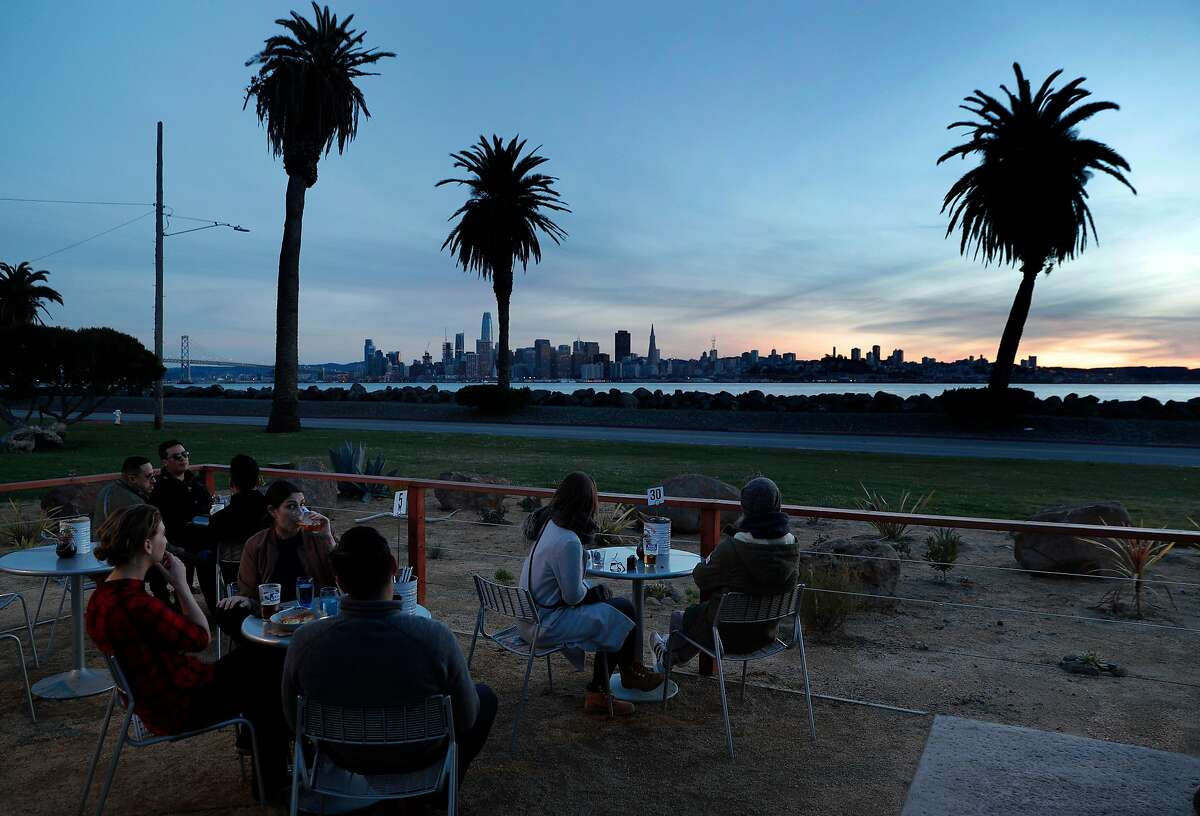 Guests enjoy the outdoor seating area at MerSea Restaurant on Treasure Island in San Francisco, Calif., on Monday, March 5, 2018. MerSea is a new restaurant (made from shipping containers) on Treasure Island with a spectacular view of the city.