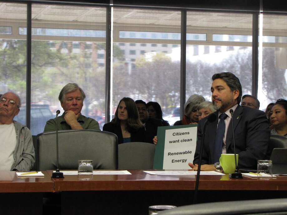 San Antonio District 1 Councilman Robert Treviño sits in front of a protester at a presentation by city owned utility CPS Energy to city council on Thursday. Questions have been raised about how fast CPS will add renewable resources to its generation mix. Photo: SAN ANTONIO EXPRESS-NEWS /Rye Druzin