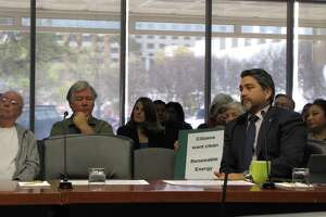San Antonio District 1 Councilman Robert Treviño sits in front of a protester at a presentation by city owned utility CPS Energy to city council on Thursday. Questions have been raised about how fast CPS will add renewable resources to its generation mix.