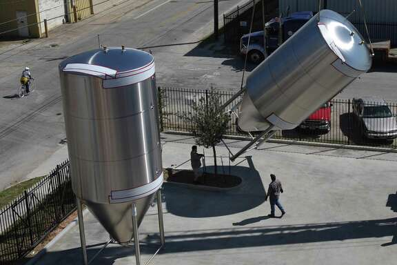 A crew from Saint Arnold Brewing Company works on unloading two large fermentation tanks that arrived at the brewing factory on Friday, Oct. 8, 2010, in Houston. Saint Arnold Brewing Company is expecting two more tanks to arrive next week and will now have 25 tanks in its factory. ( Julio Cortez / Houston Chronicle )