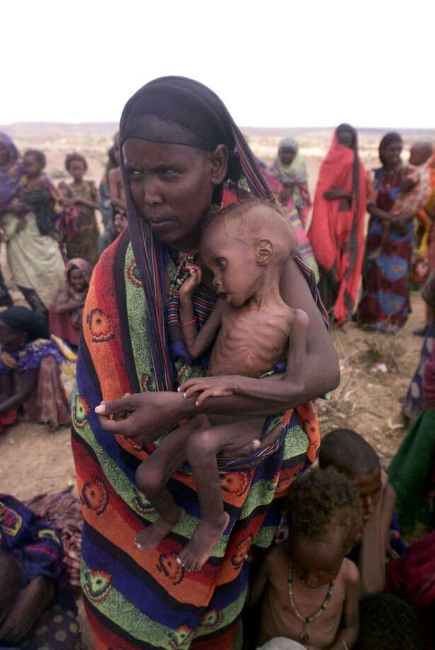 A Ethiopian woman holds her undernourished child, as she passes the time with others who like her are displaced from the countryside where they normally live due to the death of livestock on which they depend, at a makeshift displacement camp, in Hamaro, a village inside Fik district, in drought-ridden western Ethiopia, Tuesday, April 18, 2000. Photo: BRENNAN LINSLEY, STF / AP / AP