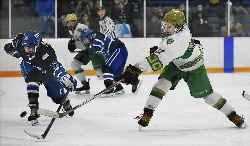Darien senior defenseman Hunter Hazelton attempts to block a shot by Notre Dame-West Haven sophomore forward Mike Bencivengo, Thursday, March 8, 2018, in the Division 1 first-round game at Bennett Rink in West Haven. Darien won, 3-2, in overtime.