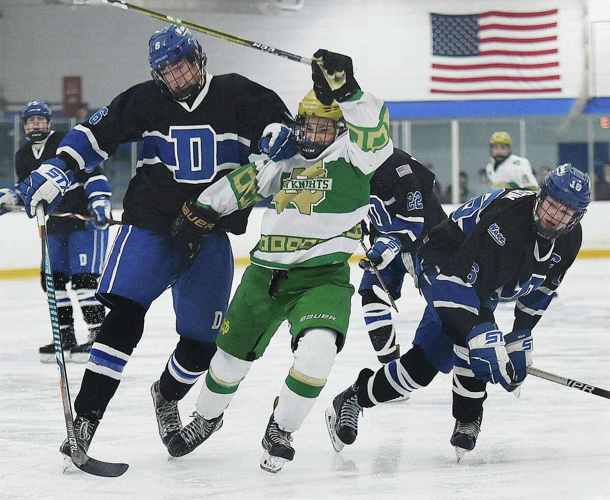 Darien's James Gregory (6) collide and captain William Dickson (16) with Notre Dame-West Haven's Chris Hibson chasing down a loose puck, Thursday, March 8, 2018, in the Division 1 first-round game at Bennett Rink in West Haven. Darien won, 3-2, in overtime.