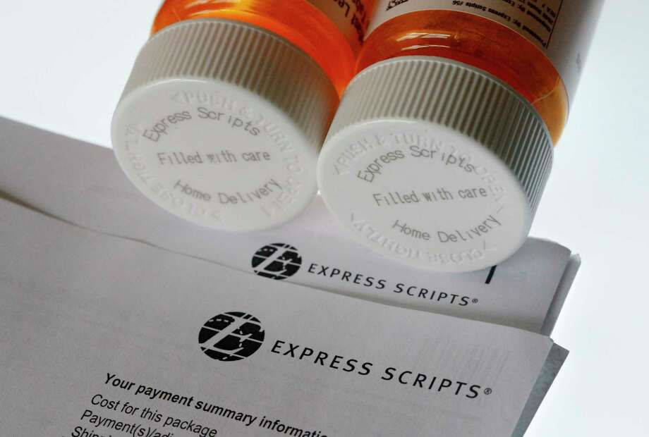FILE - In this July 25, 2017, file photo, Express Scripts prescription medication bottles are arranged for a photo in Surfside, Fla. Health insurer Cigna will spend about $52 billion to acquire the pharmacy benefits manager Express Scripts, announced Thursday, March 8, 2018, the latest in a string of proposed buyouts and tie-ups in a rapidly shifting landscape for the health services industry. (AP Photo/Wilfredo Lee, File) Photo: Wilfredo Lee / Copyright 2017 The Associated Press. All rights reserved.