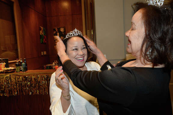 Georgine Guillory smiles as sister Morline Guillory crowns her with a tiara at the Art Museum of Southeast Texas' annual Go for Gold fundraiser at the museum Thursday. Attendees were encouraged to wear crowns and tiaras in keeping with this year's royalty theme. Each ticket was entered into a reverse drawing with the chance to win one of three prizes ranging from $1,000.00 in gold coins to a top prize of $10,000.00. Proceeds from the event benefit AMSET exhibits and programs. Photo taken Thursday, March 8, 2018 Kim Brent/The Enterprise