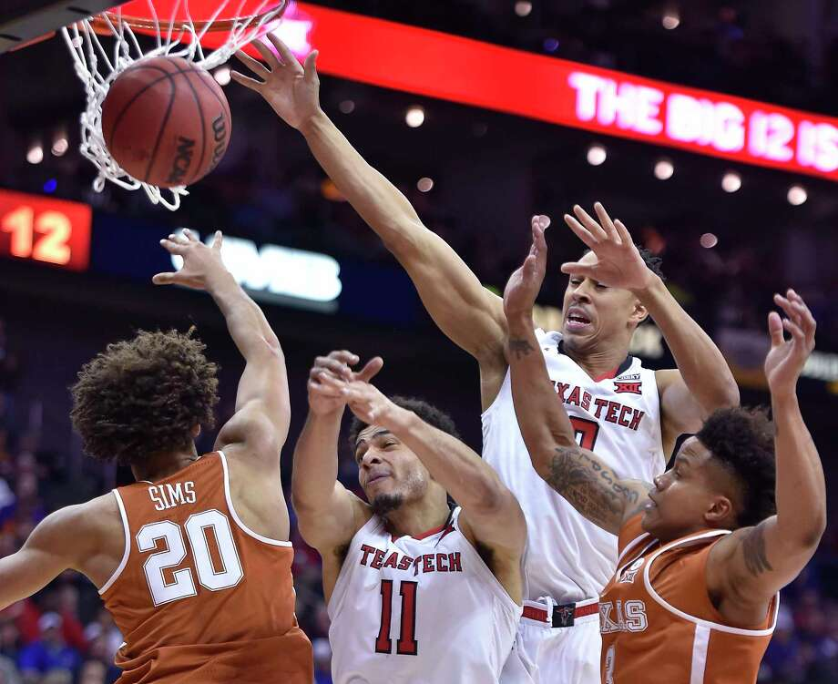 Texas' Jericho Sims (20) and teammate Jacob young, right, battle Texas Tech's Zach Smith (11) and Zhaire Smith for a rebound during the first half of a Big 12 Tournament quarterfinal at the Sprint Center in Kansas City, Mo. At rear is Texas Tech's Zach Smith. Photo: Rich Sugg, TNS / Kansas City Star