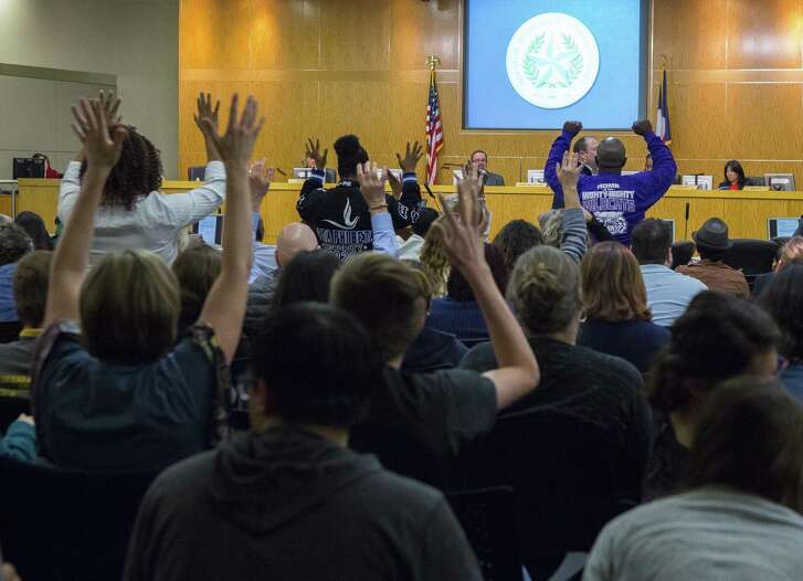 Members of the crowd at a Houston Independent School District school board meeting silently applaud a speaker during the public comment period of the meeting, Thursday, March 8, 2018, in Houston. ( Mark Mulligan / Houston Chronicle )