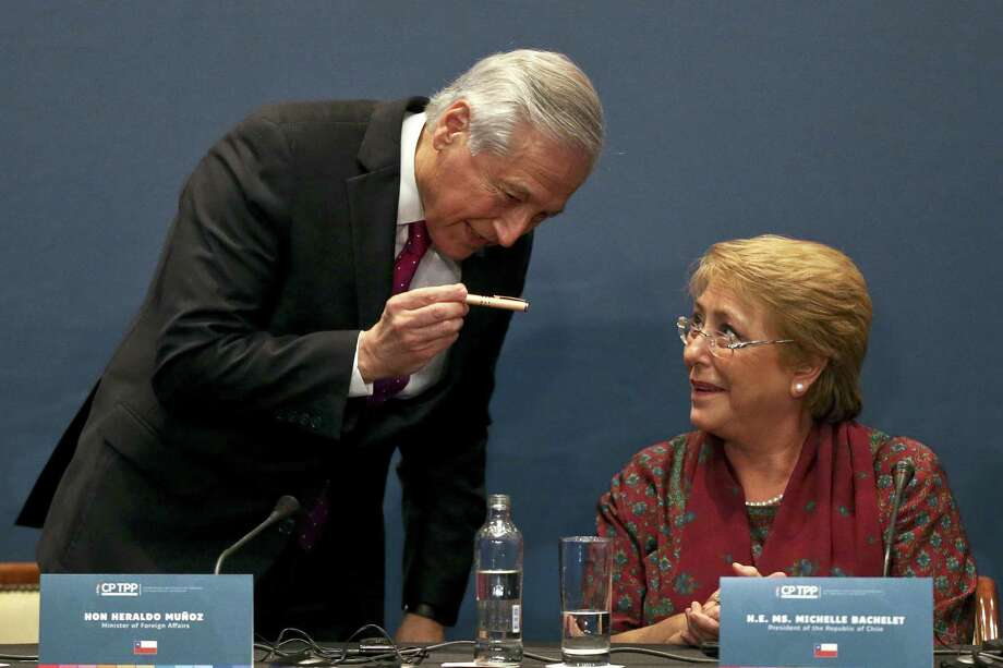 Chile's President Michelle Bachelet looks up at her Foreign Minister Heraldo Munoz, during a signing ceremony in which trade ministers from 11 Pacific Rim countries signed a sweeping free trade agreement Thursday in Santiago, Chile. Photo: Esteban Felix / Esteban Felix / Associated Press / Copyright 2018 The Associated Press. All rights reserved.