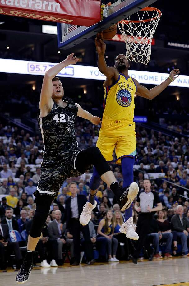 Kevin Durant blocks a shot by San Antonio's Davis Bertans. Durant had four blocks and the Warriors 12 as they overcame poor three-point shooting and an injury to Stephen Curry. Photo: Carlos Avila Gonzalez, The Chronicle