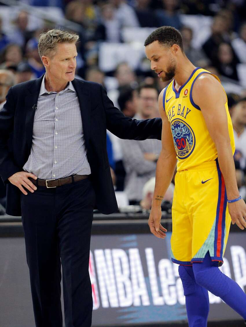 Head coach Steve Kerr checks on Stephen Curry after the two-time MVP was injured less than three minutes into the game. Curry did not return and will miss Friday's game at Portland.