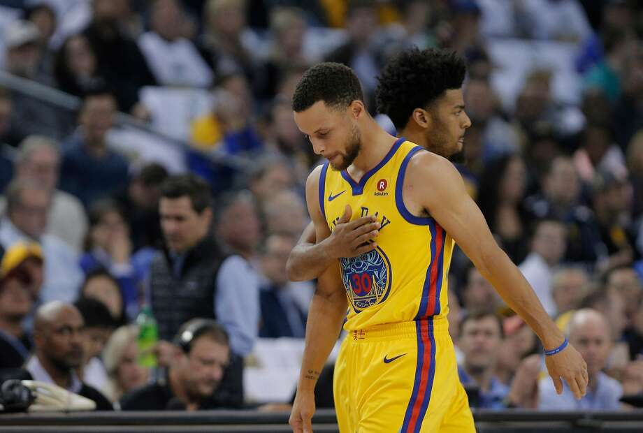 Quinn Cook (4) pats Stephen Curry (30) on the chest as Curry comes out after bing in jured in the first half as the Golden State Warriors played the San Antonio Spurs at Oracle Arena in Oakland, Calif., on Thursday, March 8, 2018. Photo: Carlos Avila Gonzalez, The Chronicle