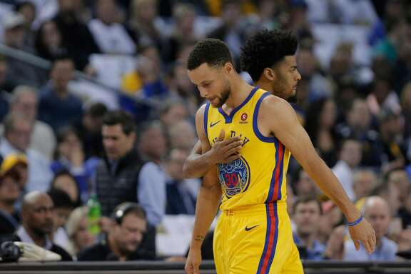 Quinn Cook (4) pats Stephen Curry (30) on the chest as Curry comes out after bing in jured in the first half as the Golden State Warriors played the San Antonio Spurs at Oracle Arena in Oakland, Calif., on Thursday, March 8, 2018.