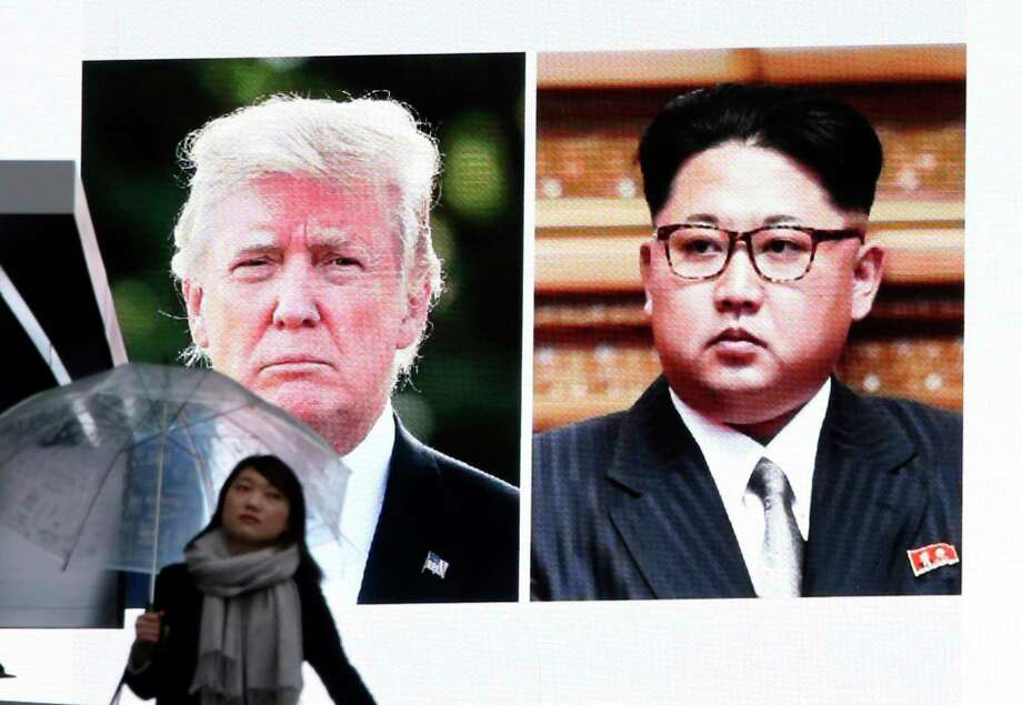 A woman walks by a huge screen showing U.S. President Donald Trump, left, and North Korea's leader Kim Jong Un, in Tokyo, Friday, March 9, 2018. After months of trading insults and threats of nuclear annihilation,  Trump agreed to meet with Kim by the end of May to negotiate an end to Pyongyang's nuclear weapons program, South Korean and U.S. officials said Thursday. No sitting American president has ever met with a North Korea leader. Photo: Koji Sasahara, AP / Copyright 2018 The Associated Press. All rights reserved.