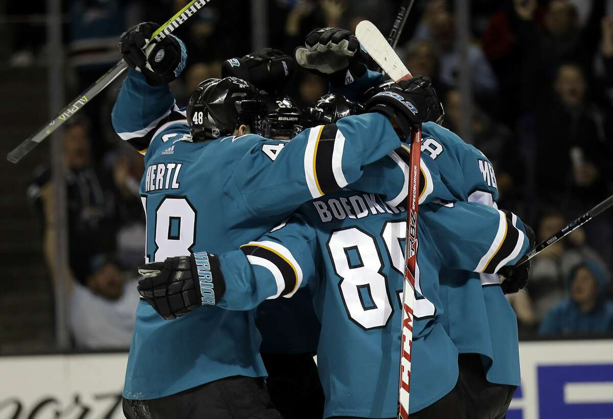 San Jose Sharks' Mikkel Boedker, center, is hugged by teammates after scoring against the St. Louis Blues during the third period of an NHL hockey game Thursday, March 8, 2018, in San Jose, Calif. (AP Photo/Marcio Jose Sanchez)
