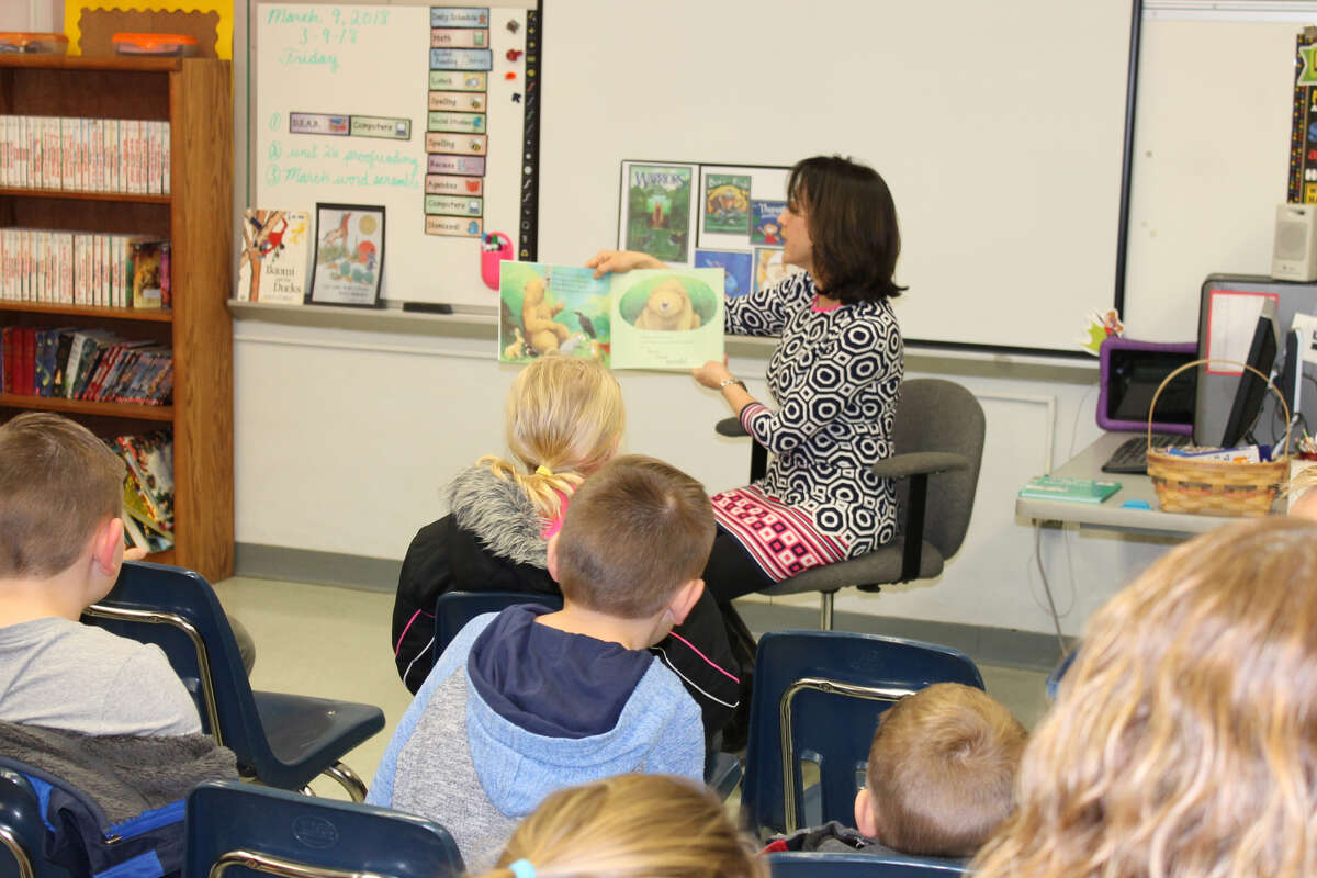 Dr. Cathy Longos, a dentist in Glen Carbon, shares a story with youngsters during Read Across America. The annual event, conducted at Woodland Elementary School, is sponsored by the Edwardsville Education Association, Alpha Delta Kappa teachers' sorority and Edwardsville District 7.