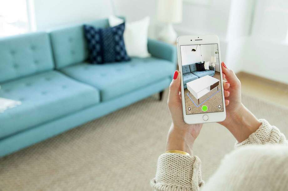 This March 2018 photo provided by Houzz shows their View in My Room 3D, an augmented reality tool in the Houzz app that lets people preview over 1 million furniture and decor products from the Houzz Shop in 3D, within their homes, before they buy. (Houzz via AP) / Houzz