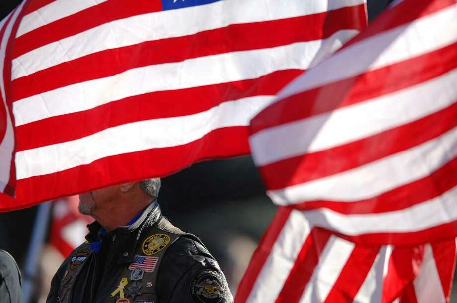 Members of the Patriot Guard Riders on Tuesday line the sidewalk holding flags outside Reach Out Fellowship church in Colonie for the funeral of Army Staff Sgt. Amy Seyboth Tirador, who died in Iraq. (Paul Buckowski / Times Union) Photo: PAUL BUCKOWSKI / 00006404A