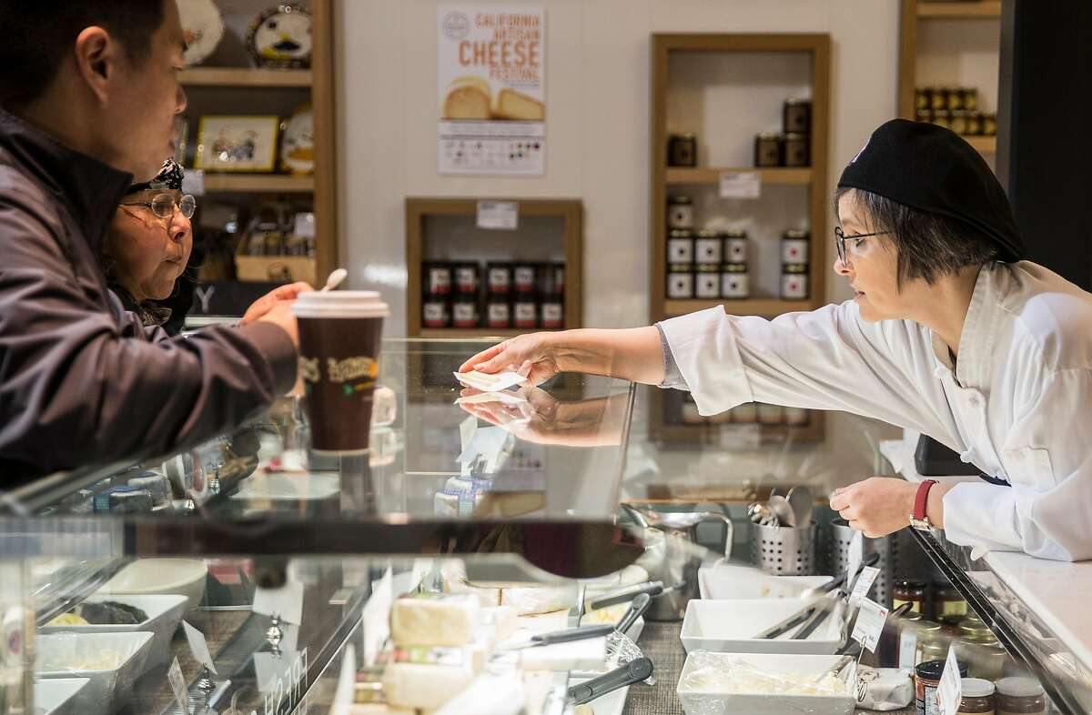 A woman hands out samples at Cowgirl Creamery inside the Ferry Building Saturday, March 3, 2018 in San Francisco, Calif.