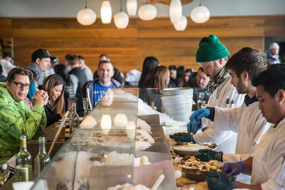 Cooks schuck oysters at Hog Island Oyster Company inside the Ferry Building Saturday, March 3, 2018 in San Francisco, Calif.
