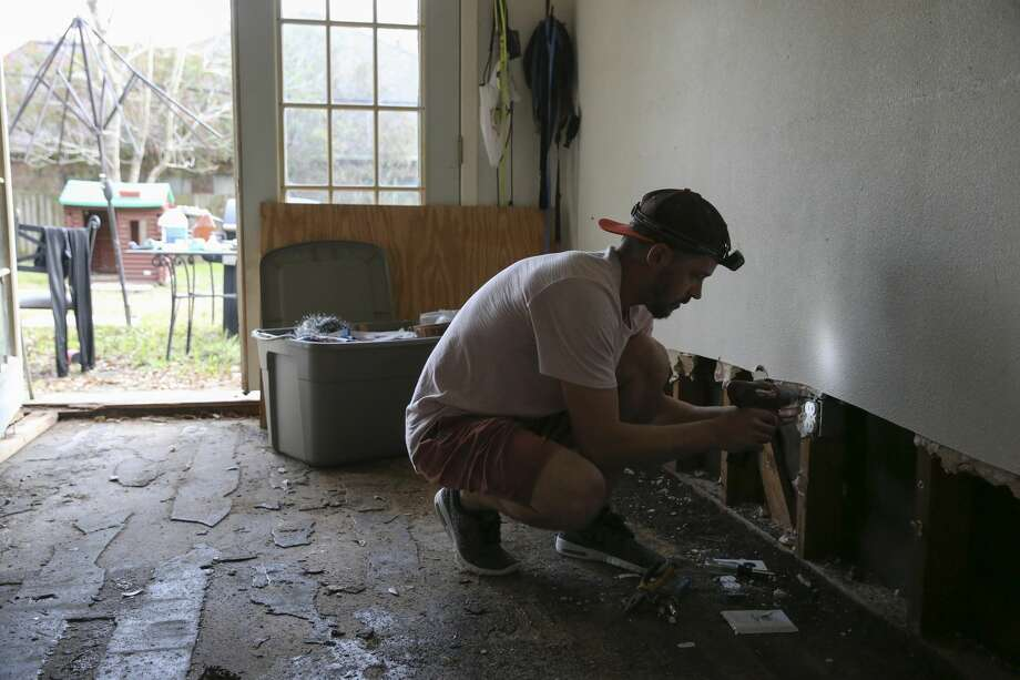 Electrician Brad Cochran changes electric receptacle for Tracy Wilson's flooded and gutted house in Houston. On the same day, Wilson met a representative from a sub-contractor for PREPS, which is a FEMA housing program that provides up to $20,000 in repair work for flooded homes, to discuss rebuilding her house. Photo: Yi-Chin Lee/Houston Chronicle