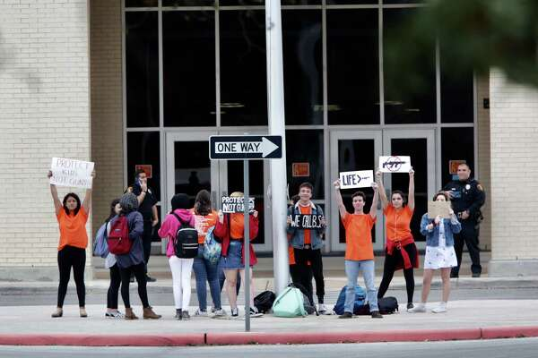 A group of student at Brandeis HS hold up protest signs in front of the school, voicing their opinions against guns, on Friday, March 9, 2018.