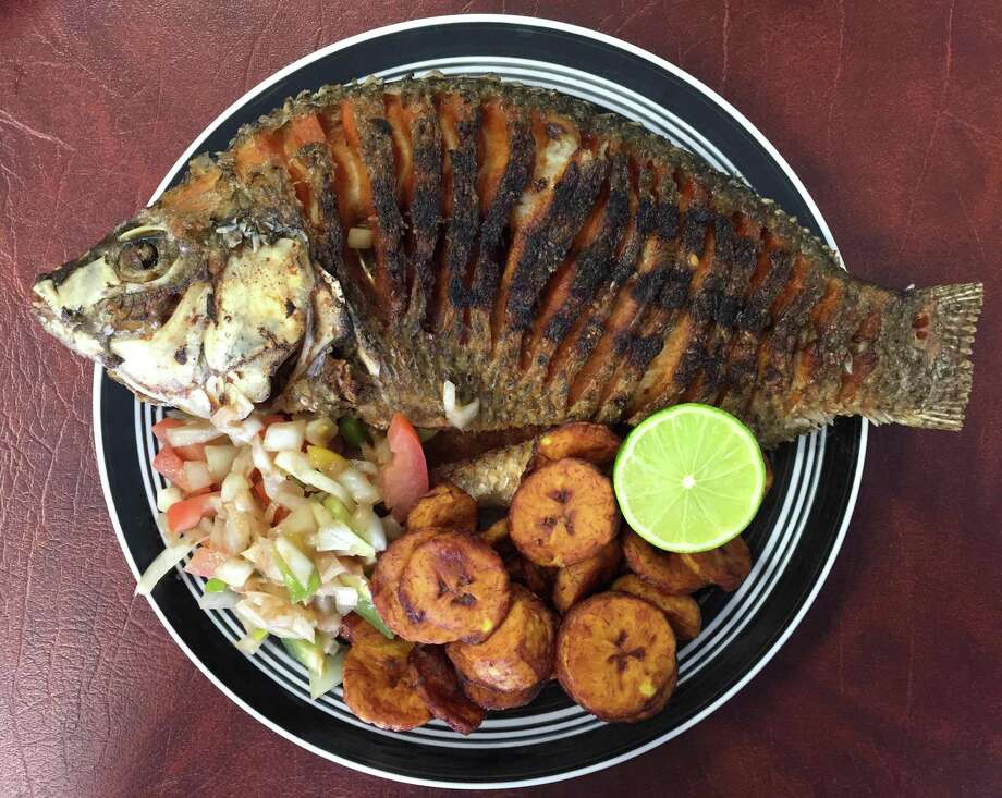 Poisson braise, a whole fried tilapia, from Kaedi Dimbe African Cuisine. Photo: Paul Stephen / San Antonio Express-News