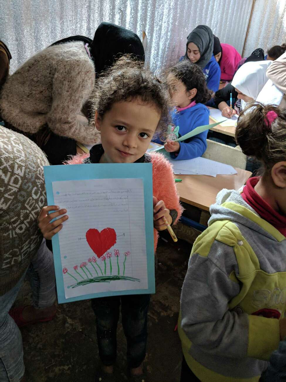 Syrian children hold up the letters they wrote for students of the Hudson City School District at the Ketermaya Refugee Camp in Lebanon. (Photo courtesy of Danette Gorman)
