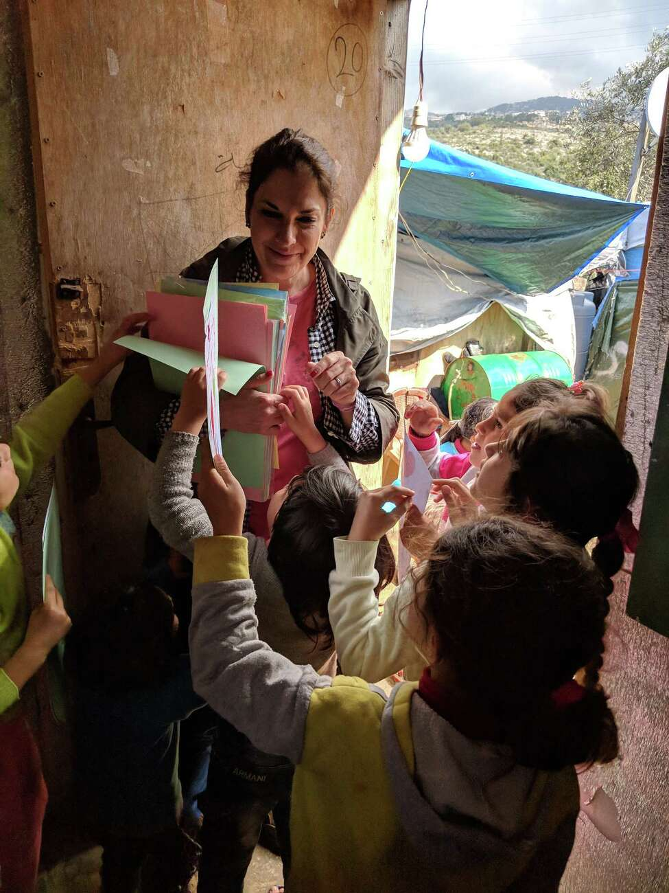 Danette Gorman distributes letters written by students of the Hudson City School District to Syrian children at the Ketermaya Refugee Camp. (Photo courtesy of Danette Gorman)