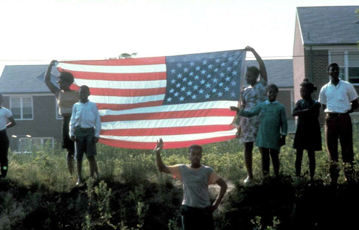 UNSPECIFIED - JUNE 1968: Group with Amer. flag standing on hillside watching passing of funeral train (unseen) of slain presidential candidate Senator Robert Kennedy, on it's way to burial in Arlington National Cemetery. (Photo by Bill Eppridge/Time & Life Pictures/Getty Images)