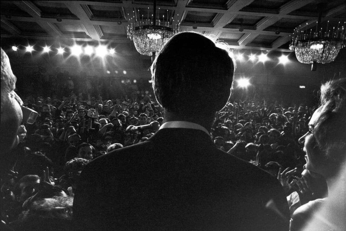 Subject: Rear view of Senator Robert Kennedy and wife Ethel as he stands at podium, addressing his constituents and the press after his California primary election victory at the Ambassador Hotel prior to his assassination. Los Angeles California June 5 1968 Photographer- Bill Eppridge Time Inc Owned Merlin-155216