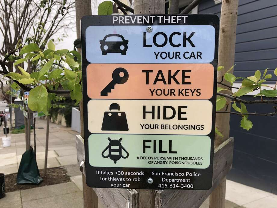 """Humorous signs near Alamo Square Park in San Francisco warn drivers to lock their cars, remove their valuables and """"fill a decoy purse with thousands of angry, poisonous bees."""" Photo: Michelle Robertson/SFGATE"""